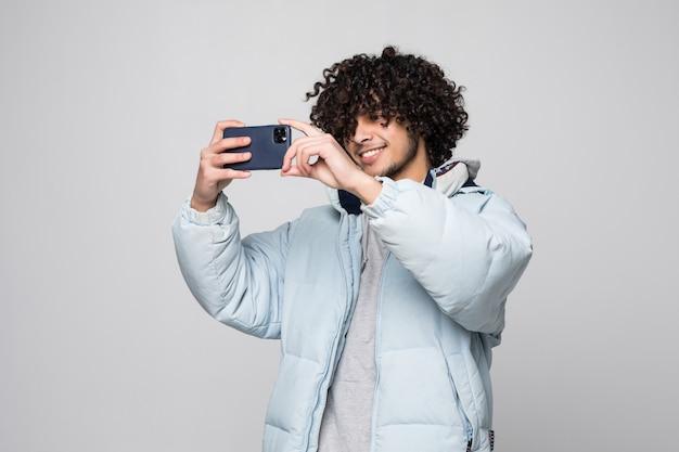 Jeune Homme Aux Cheveux Bouclés à L'aide De Téléphone Portable Sur Un Mur Blanc Isolé Photo gratuit