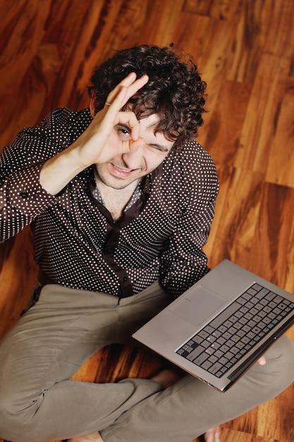 Un jeune homme aux cheveux bouclés est assis devant un ordinateur portable sur le sol chaud. idée créative, créateur, designer Photo Premium