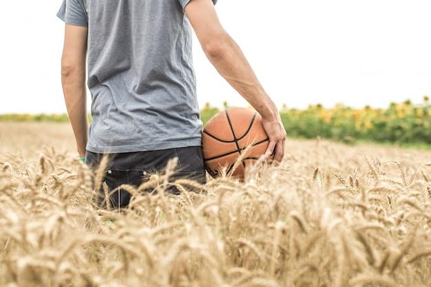 Jeune Homme Avec Un Ballon De Basket Sur La Nature, Le Concept De Sport Photo gratuit