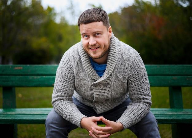 Jeune homme sur le banc avec les mains jointes Photo gratuit