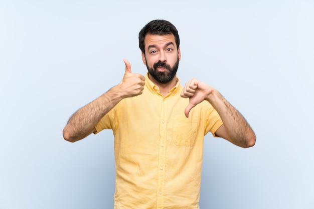 Jeune homme à la barbe sur le bleu fait bon signe. indécis entre oui ou non Photo Premium