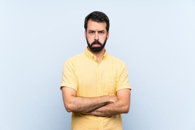 Jeune homme à la barbe sur bleu isolé avec une expression triste et déprimée Photo Premium