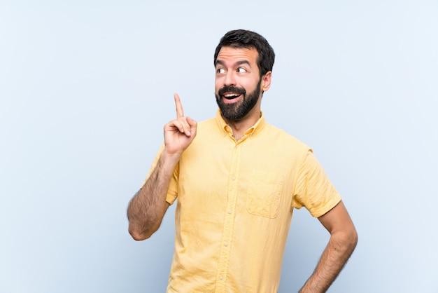 Jeune Homme à La Barbe Sur Bleu Pensant Une Idée Pointant Le Doigt Vers Le Haut Photo Premium