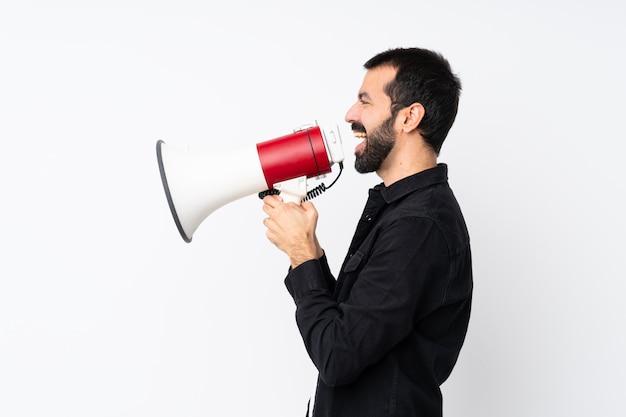 Jeune homme à la barbe sur mur blanc isolé, criant à travers un mégaphone Photo Premium