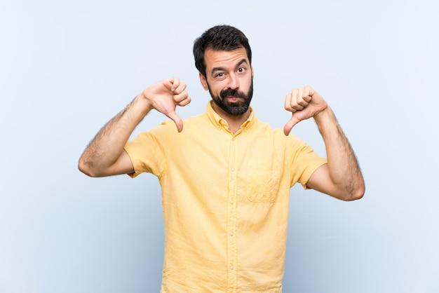 Jeune Homme à La Barbe Sur Mur Bleu Isolé, Montrant Le Pouce Vers Le Bas Photo Premium