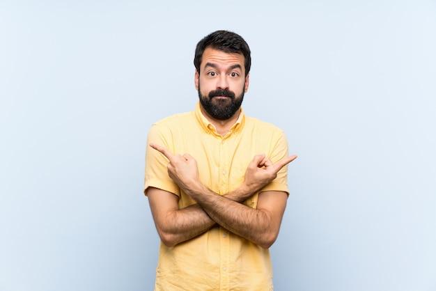 Jeune homme à la barbe sur mur bleu isolé, pointant vers les côtés ayant des doutes Photo Premium