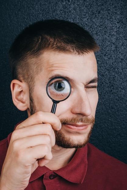 Un jeune homme avec une barbe regarde à travers une loupe. Photo Premium