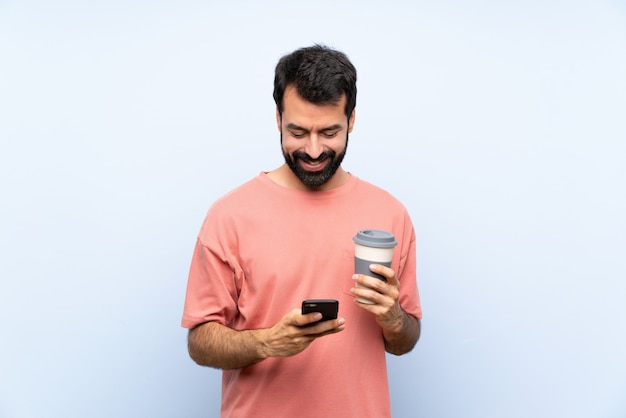 Jeune homme à la barbe tenant un café à emporter sur bleu isolé, envoyant un message avec le téléphone portable Photo Premium