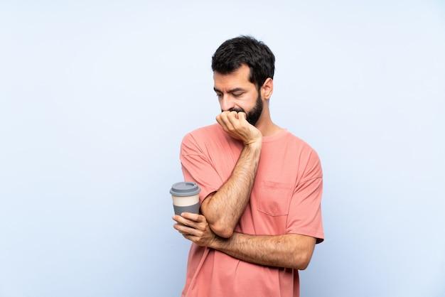Jeune homme à la barbe tenant un café à emporter sur un mur bleu isolé ayant des doutes Photo Premium