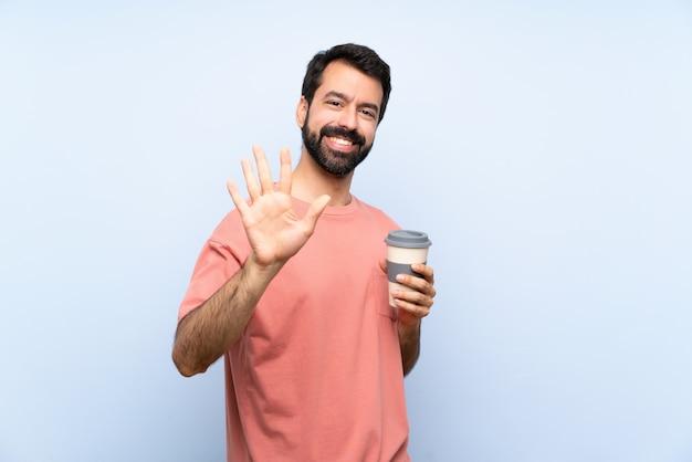 Jeune homme à la barbe tenant un café à emporter sur un mur bleu isolé comptant cinq avec les doigts Photo Premium