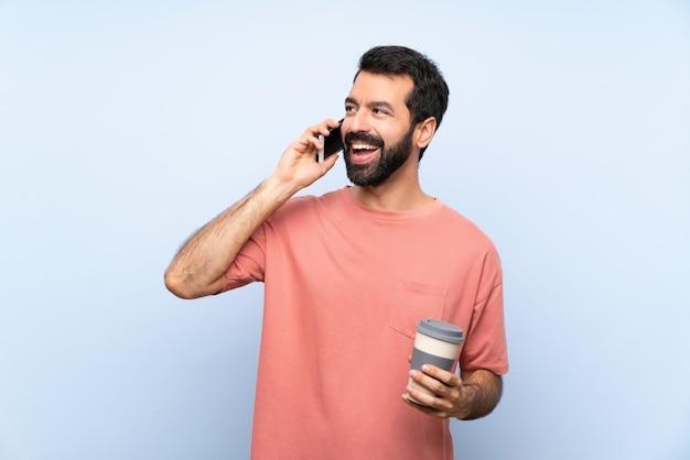 Jeune homme à la barbe tenant un café à emporter sur un mur bleu isolé, gardant la conversation avec le téléphone portable Photo Premium