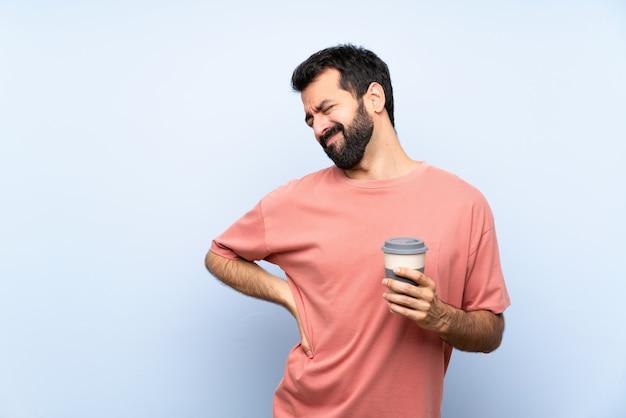 Jeune homme à la barbe tenant un café à emporter sur un mur bleu isolé souffrant de maux de dos Photo Premium