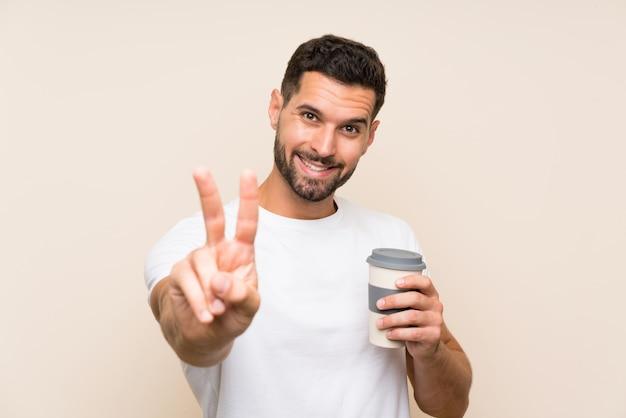 Jeune homme à la barbe tenant un café à emporter sur un mur bleu isolé, souriant et en montrant le signe de la victoire Photo Premium