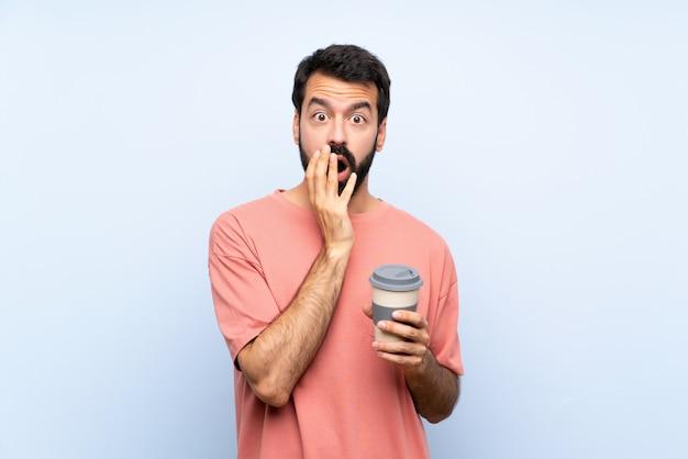 Jeune homme à la barbe tenant un café à emporter sur un mur bleu isolé surpris et choqué tout en regardant à droite Photo Premium