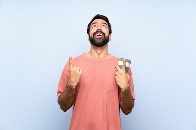 Jeune homme à la barbe tenant un café à emporter sur un mur bleu isolé surpris et pointant vers le haut Photo Premium