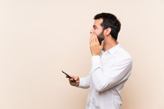 Jeune homme à la barbe tenant un mobile en criant avec la bouche grande ouverte sur le côté Photo Premium