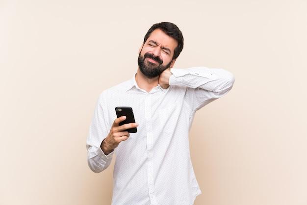 Jeune homme à la barbe tenant un mobile avec maux de cou Photo Premium