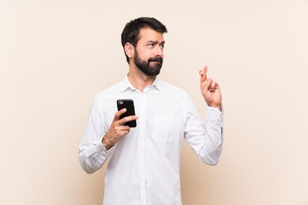 Jeune homme à la barbe tenant un téléphone portable avec les doigts qui se croisent et souhaitant le meilleur Photo Premium