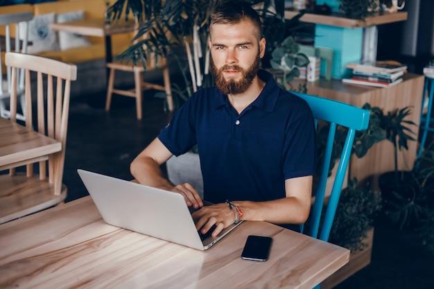Jeune homme avec une barbe travaille dans un café, pigiste utilise un ordinateur portable, fait un projet Photo gratuit