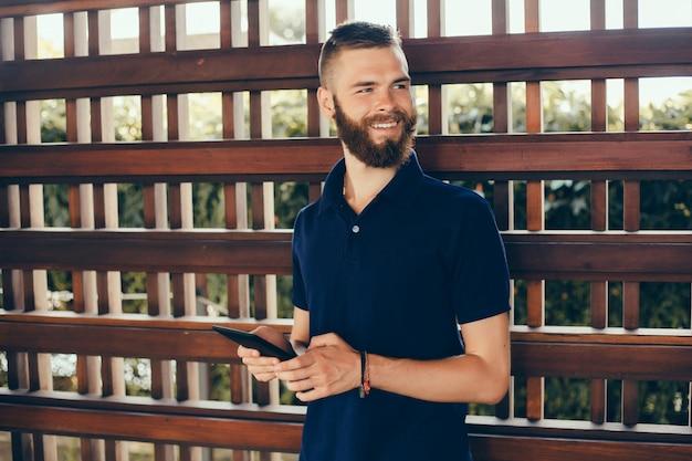 Jeune homme avec une barbe travaille dans un café, pigiste utilise une tablette, fait un projet Photo gratuit