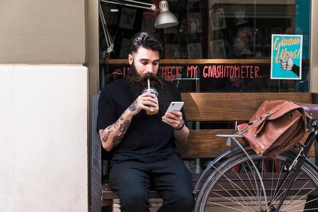 Jeune homme barbu assis sur un banc à l'extérieur du café buvant une boisson au chocolat à l'aide d'un téléphone portable Photo gratuit
