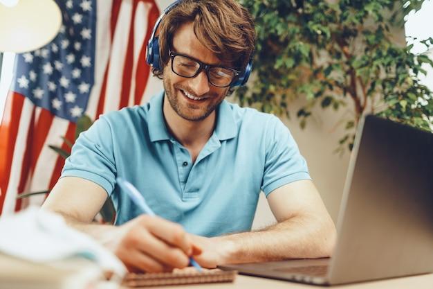 Jeune Homme Barbu Assis à Table Avec Ordinateur Portable Et Drapeau Américain Photo Premium