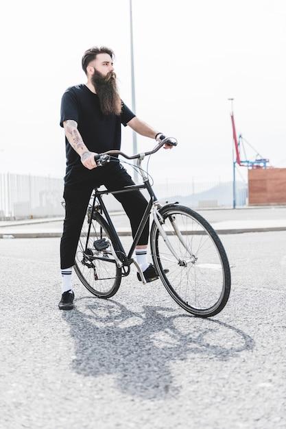 Jeune homme barbu assis sur un vélo à la recherche de suite Photo gratuit