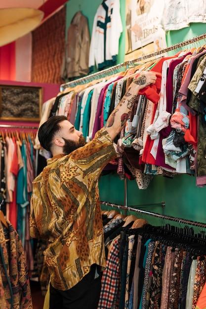 Jeune homme barbu choisissant un t-shirt rouge dans la boutique de vêtements Photo gratuit