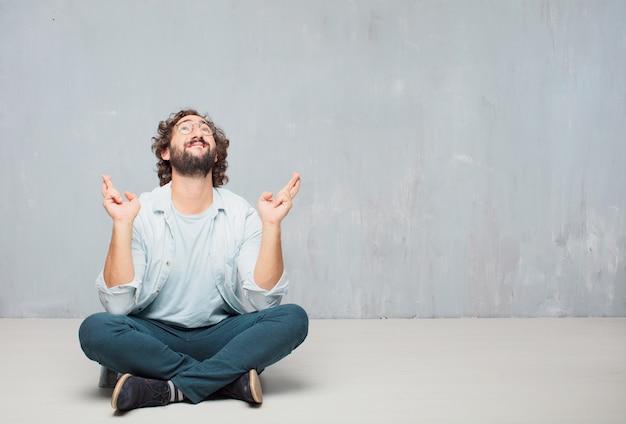 Jeune homme barbu cool assis sur le sol. fond de mur de grunge Photo Premium