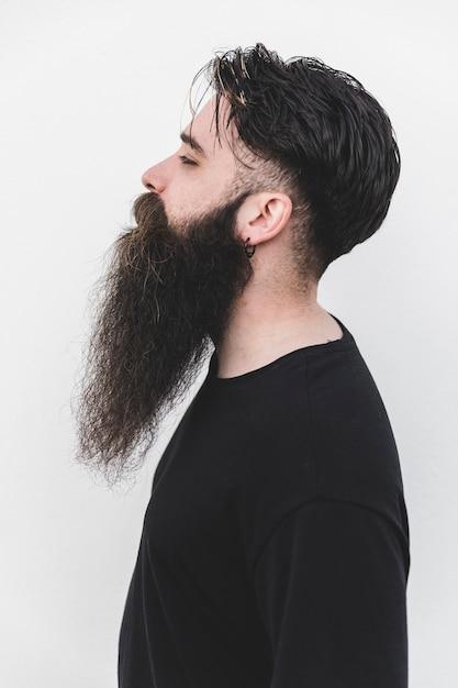 Jeune homme barbu debout contre un fond blanc Photo gratuit