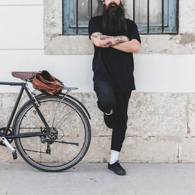 Jeune homme barbu debout contre le mur, les bras croisés Photo gratuit