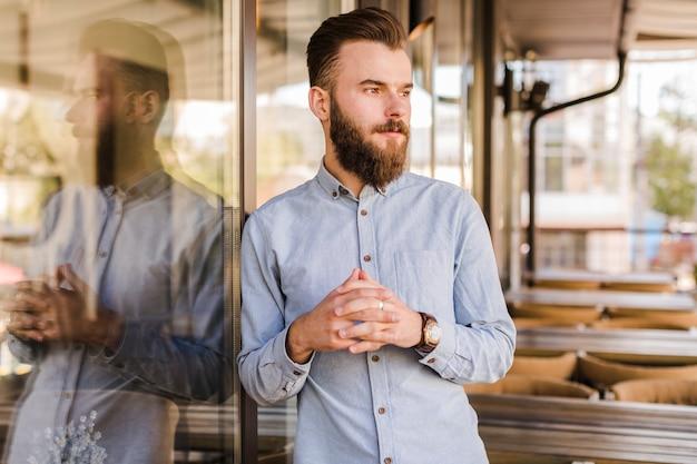 Jeune homme barbu debout dans un restaurant Photo gratuit