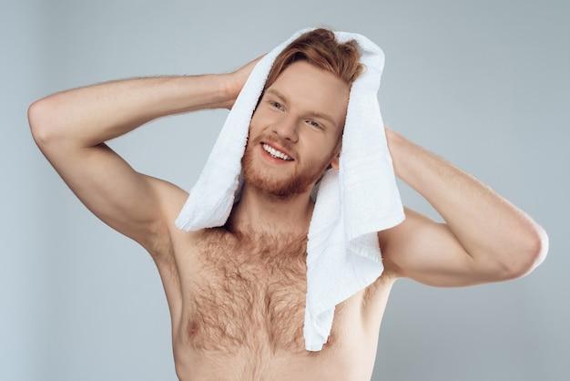Jeune homme barbu essuyant les cheveux mouillés par une serviette Photo Premium