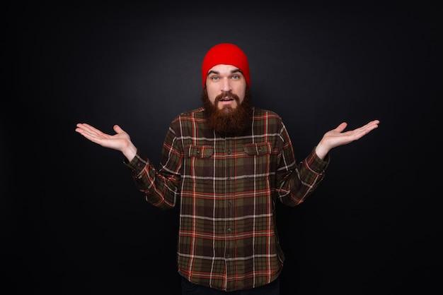 Jeune Homme Barbu Faisant Je Ne Sais Pas Le Geste. Hipster Portant Un Chapeau De Laine Rouge Sur Fond Noir. Photo Premium