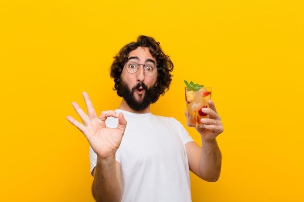 Jeune homme barbu fou avec un cocktail. touristique Photo Premium