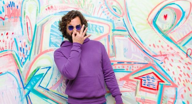 Jeune homme barbu fou se sentant dégoûté, tenant son nez pour éviter de sentir une odeur nauséabonde et désagréable contre le mur de graffitis Photo Premium
