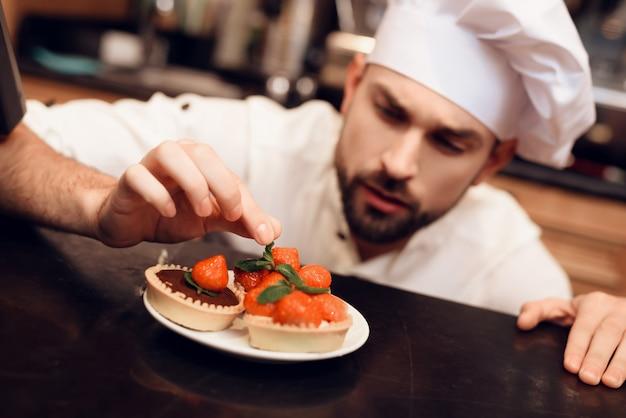 Jeune homme barbu avec gâteau debout dans la boulangerie Photo Premium
