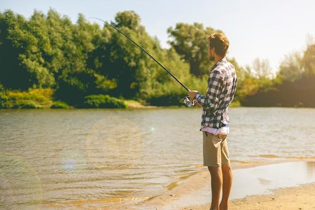 Jeune homme barbu pêchant debout sur la rive sablonneuse avec une canne à poisson en été. Photo Premium