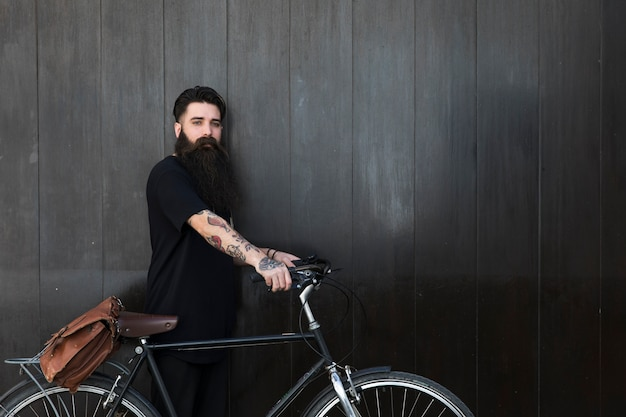 Jeune homme barbu avec son vélo devant un mur en bois noir Photo gratuit