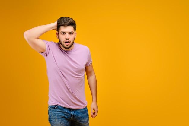Jeune homme barbu, tenant sa tête surprise isolée sur fond jaune Photo Premium