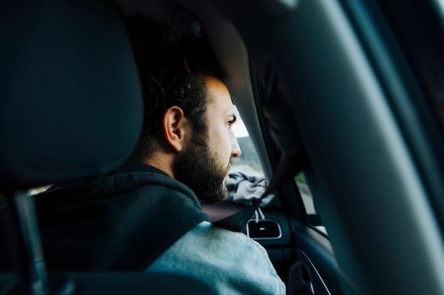 Jeune homme barbu voyageant en voiture Photo gratuit