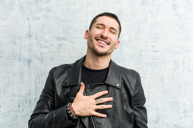 Jeune homme à bascule éclate de rire en gardant la main sur la poitrine. Photo Premium