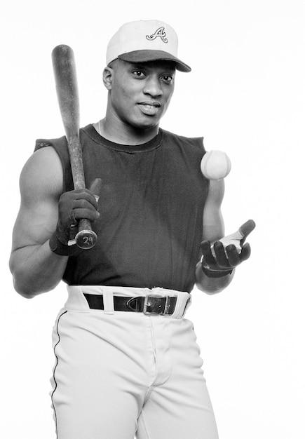Jeune homme avec batte de baseball et balle, souriant, portrait (n & b) Photo Premium