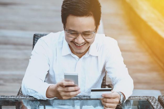 Le Jeune Homme Beau Apprécie Faire Des Achats En Ligne Sur Un Téléphone Mobile Avec Une Carte De Crédit. Photo gratuit