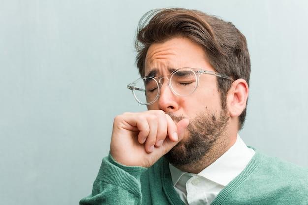 Jeune homme beau entrepreneur visage agrandi avec un mal de gorge, malade en raison d'un virus, fatigué et débordé Photo Premium