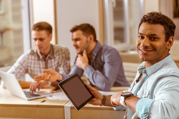 Jeune homme beau mulâtre souriant sur le lieu de travail. Photo Premium