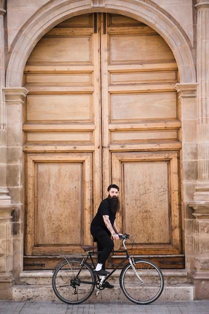Jeune homme à bicyclette devant la grande porte fermée Photo gratuit