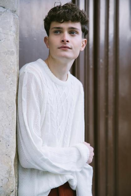 Jeune homme en blanc regardant de côté Photo gratuit