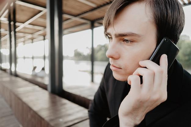 Jeune Homme Blanc Tient Un Smartphone à La Main. Photo Premium
