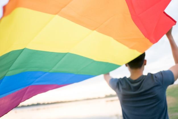 Un jeune homme blanc voit par derrière tenant un drapeau arc-en-ciel sur sa tête. Photo Premium